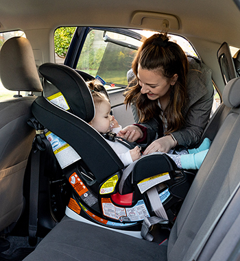 Mom adjusting seat belt for infant car seat
