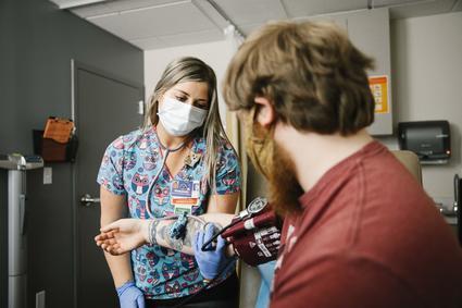 Asistente médico midiendo la presión arterial de un paciente