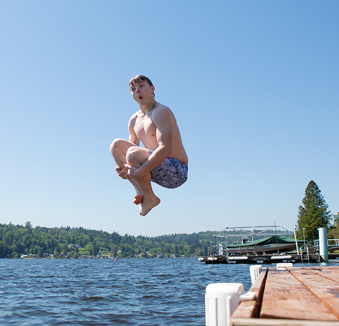 Boy jumping off dock