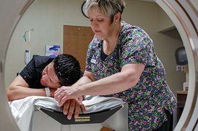 Técnica prepara a paciente para un estudio