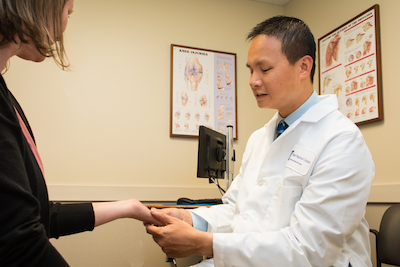 Dr. Dang examines a patient's wrist