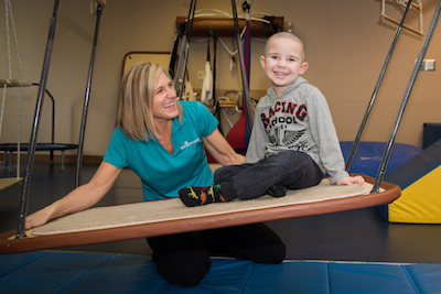 Physical therapist with young boy